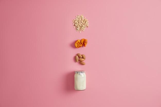 Gezond dieet voedselconcept. glazen pot met verse yoghurt, havergranen, gedroogde abrikozen en amandelnoten voor het bereiden van ontbijtmaaltijd. goede voeding. ingrediënten om heerlijke zelfgemaakte havermout te maken