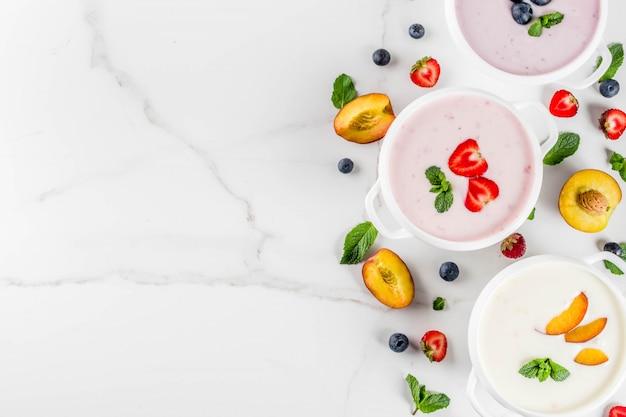 Gezond diner in de zomer, veganistisch eten, dessert, verschillende zoete romige fruit- en bessensoepen