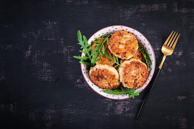 Gezond diner. kippenkoteletten in een kom op een donkere achtergrond. bovenaanzicht, plat gelegd