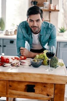 Gezond diner koken. knappe jongeman in vrijetijdskleding die naar de camera kijkt en glimlacht terwijl hij thuis in de keuken staat