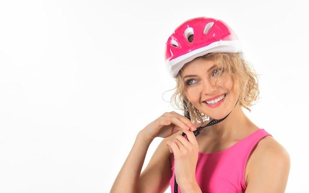 Gezond en actief concept sportmeisje maakt stijlvolle roze schaatshelm sportvrouw vast in beschermend