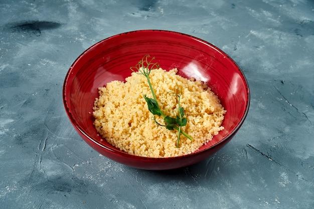 Gezond en dieetbijgerecht - couscouspap in een bordeauxrode kom op een concrete oppervlakte