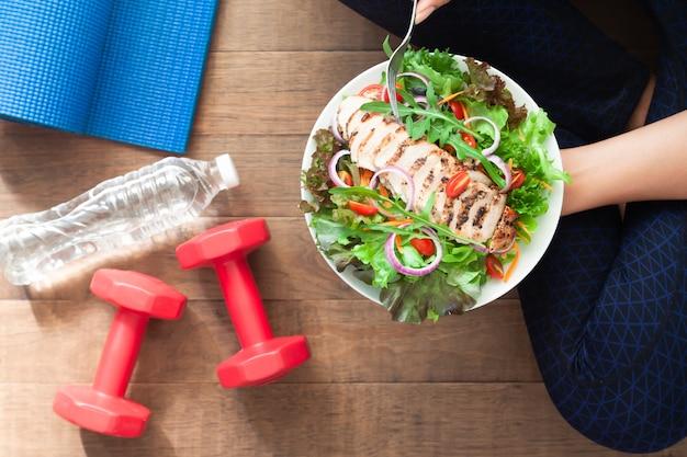 Gezond en fitness eten. kipsaladeschotel met fitnessapparatuur