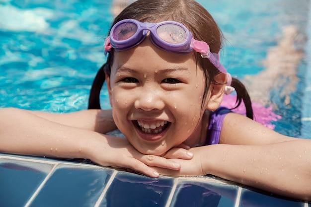 Gezond en gelukkig aziatisch meisje dat beschermende brillen in zwembad draagt