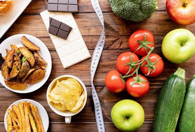 Gezond en ongezond voedsel concept. groenten en fruit vs snoepjes en aardappel frietjes bovenaanzicht plat lag op houten tafel