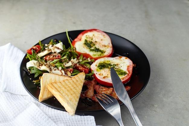 Gezond en smakelijk ontbijt. gebakken eieren in ringen van rode peper, spek en salade met rucola, kerstomaatjes, zaden en harde kaas op zwarte plaat