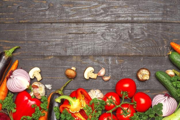 Gezond eten achtergrond. de verschillende groenten van de voedselfotografie op donkere houten achtergrond