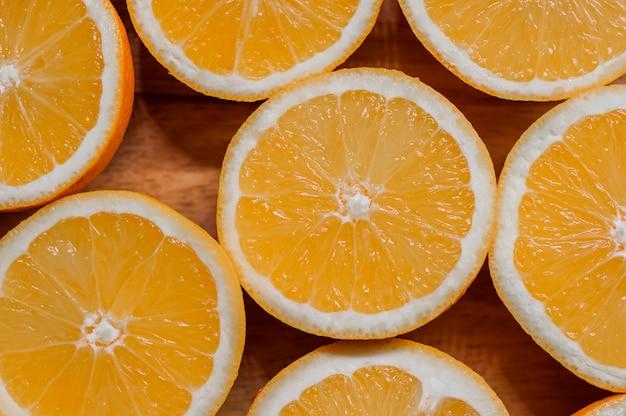 Gezond eten, achtergrond. sinaasappelschijfjes als achtergrondtextuur. gesneden verse sinaasappelen in vorm op houten achtergrond ingericht