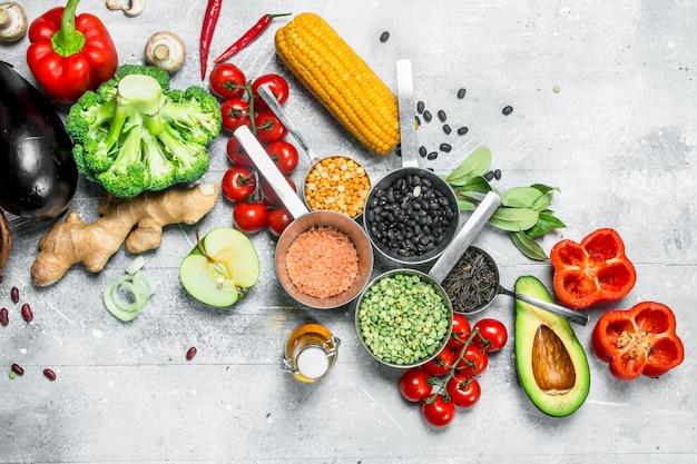 Gezond eten. assortiment van biologische groenten en fruit met peulvruchten op een rustieke tafel.