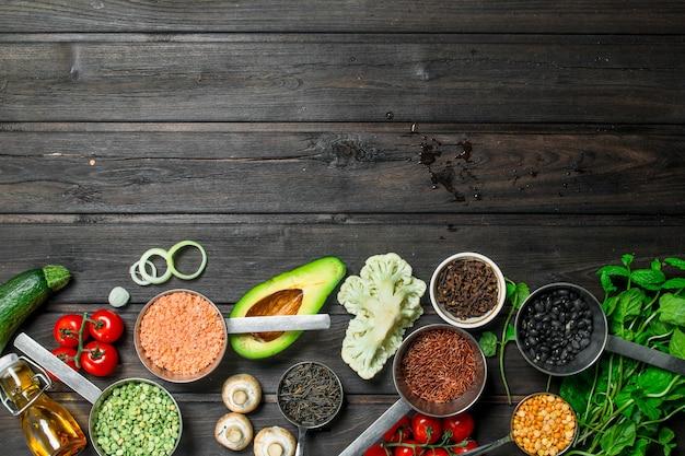 Gezond eten. assortiment van granen met peulvruchten en biologische groenten op rustieke tafel.