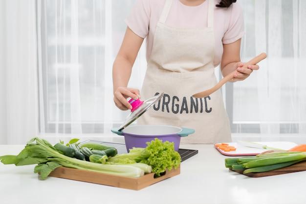 Gezond eten. aziatische vrouw koken in de keuken met houten lepel