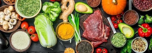 Gezond eten. biologisch voedselassortiment met rauwe biefstuk op rustieke tafel.