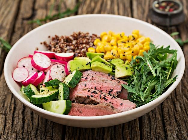 Gezond eten. boeddha kom lunch met gegrilde biefstuk en quinoa, maïs, avocado, komkommer en rucola op houten tafel. vleessalade.