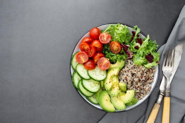 Gezond eten. budha kom met quinoa, avocado, komkommer, salade, tomaat, olijfolie.