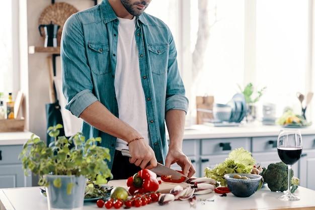 Gezond eten. close-up van een jonge man in vrijetijdskleding die groenten snijdt terwijl hij thuis in de keuken staat
