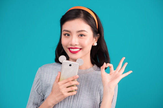 Gezond eten. close-up van lachende mooie pinup aziatisch meisje met smartphone over blauwe achtergrond.