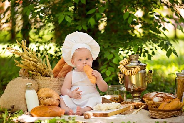 Gezond eten concept. de bakker van de peuterjongen zit en maakt deeg, eet brood met melk in een witte schort en een hoed.