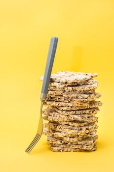Gezond eten. crispread gemaakt van haver, tarwe, lijnzaad en sesamzaad in een stapel en een vork op een gele achtergrond. superfood. verticale weergave