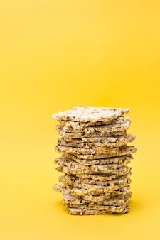 Gezond eten. crispread gemaakt van haver, tarwe, lijnzaad en sesamzaad in een stapel op een gele achtergrond. superfood. verticale weergave
