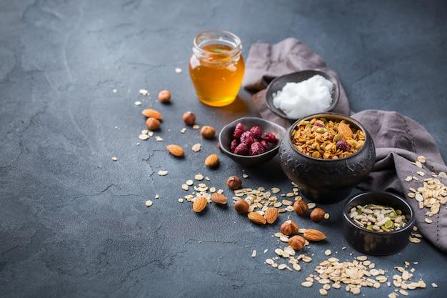 Gezond eten, dieet en voeding, fitness, evenwichtige voeding, ontbijtconcept. zelfgemaakte muesli muesli met ingrediënten op een tafel. ruimte achtergrond kopiëren