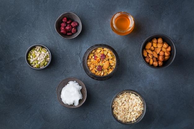 Gezond eten, dieet en voeding, fitness, evenwichtige voeding, ontbijtconcept. zelfgemaakte muesli muesli met ingrediënten op een tafel.