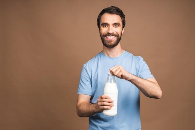 Gezond eten, dieetconcept! portret van jonge, bebaarde man met een fles melk geïsoleerd over beige achtergrond.