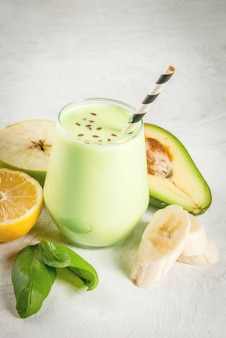 Gezond eten. dieetontbijt of snack. groene smoothies van yoghurt, avocado, banaan, appel, spinazie en citroen. op witte betonnen stenen tafel, met ingrediënten. copyspace