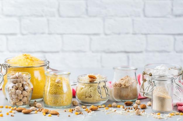 Gezond eten, diëten, uitgebalanceerd voedselconcept. assortiment van glutenvrij meel, amandel, maïs, rijst op een keukentafel. ruimte achtergrond kopiëren