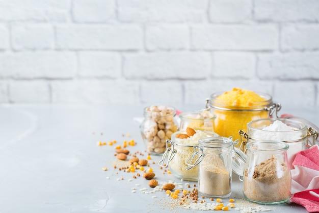 Gezond eten, diëten, uitgebalanceerd voedselconcept. assortiment van glutenvrij voedsel en meel, amandel, maïs, rijst op een houten tafel. ruimte achtergrond kopiëren