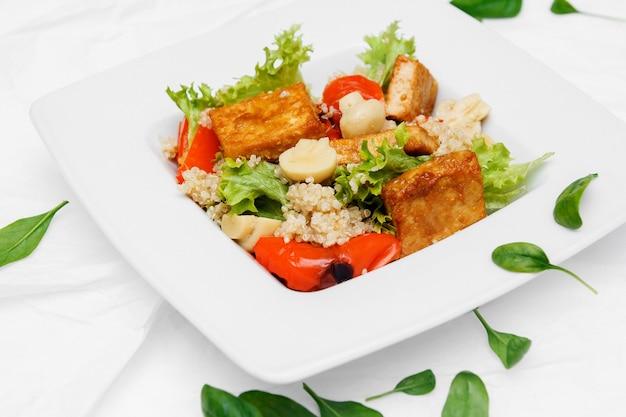 Gezond eten. een witte borden. tomatensalade, rucola, spinazie, olijven, peper. witte achtergrond