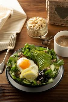 Gezond eten. eieren, quinoa, avocado, groene salade, zwarte olijven. houten tafel. dieet, afvallen.