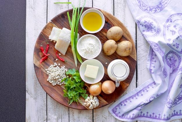 Gezond eten en dieet concept - natuurlijke voeding op tafel. ingrediënten vis bonen peterselie uien crème aardappelen voor gehaktballen