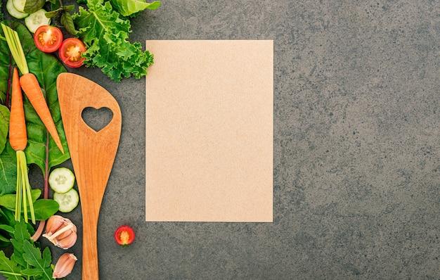 Gezond eten en koken concept houten spatel en groenten op donkere steen.