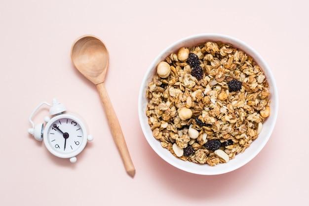 Gezond eten. gebakken haver, noten en rozijnengranola in een kom, wekker en een houten lepel op een roze oppervlakte. bovenaanzicht