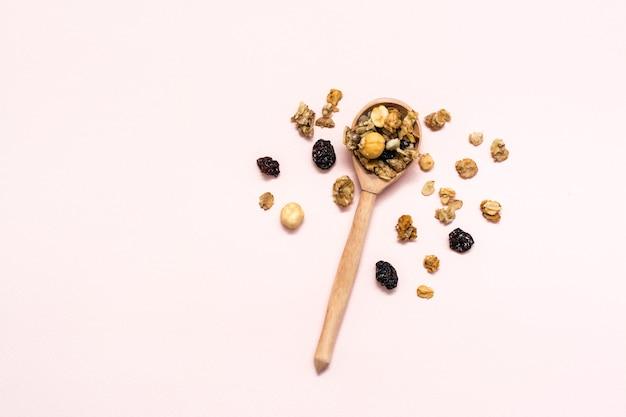 Gezond eten. gebakken muesli van haver, noten en rozijnen in een houten lepel op een roze achtergrond. bovenaanzicht