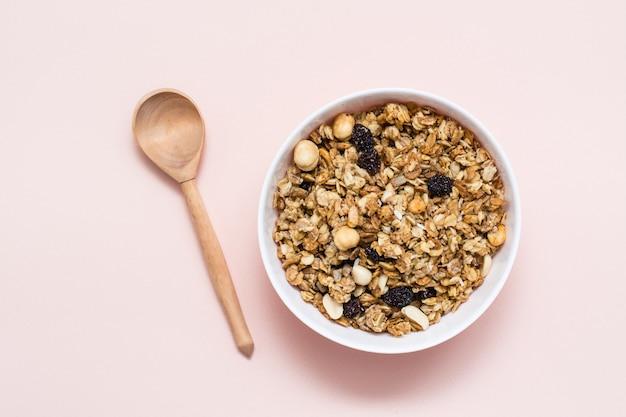 Gezond eten. gebakken muesli van haver, noten en rozijnen in een kom en een houten lepel op een roze ondergrond. bovenaanzicht