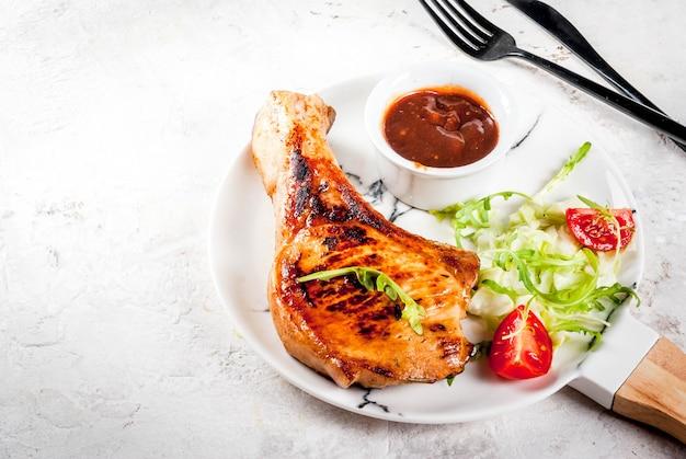 Gezond eten. gedeelte van verse salade met tomaten, rucola, slabladeren, kool en gegrild varkensvlees