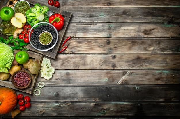 Gezond eten. gezond assortiment van groenten en fruit met peulvruchten. op een houten tafel.