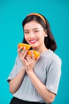 Gezond eten. glimlachend mooi pinup aziatisch meisje dat sinaasappel over blauwe achtergrond houdt.