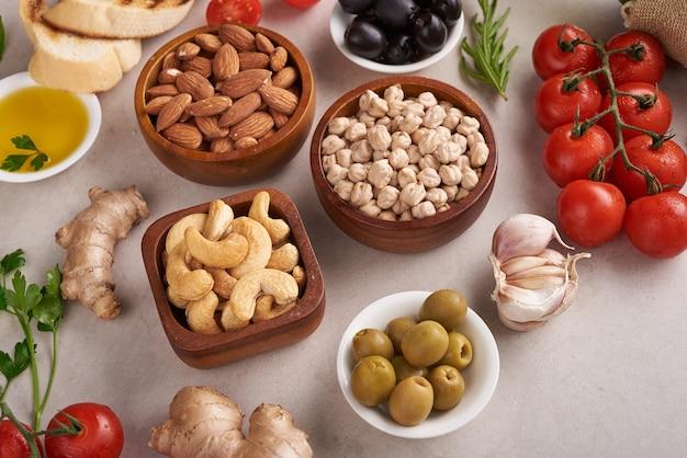 Gezond eten. groenten, citroen en kikkererwten op betonnen ondergrond, vegetarisch eten of mediterraan keukenconcept, kopie ruimte. fruit, groenten, graan, noten olijfolie op houten tafel.