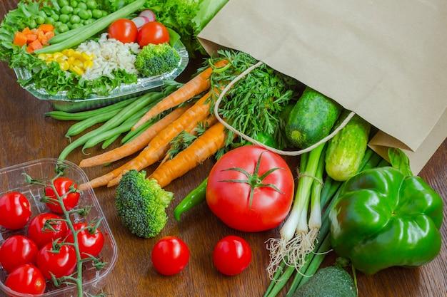 Gezond eten in volle papieren zak met verschillende producten, groenten. bovenaanzicht.