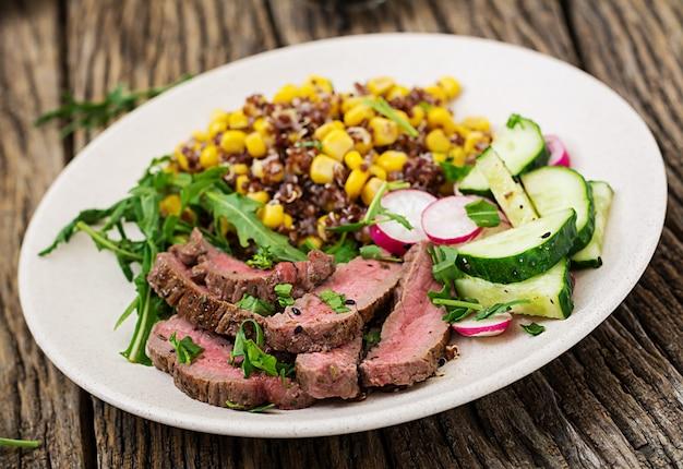 Gezond eten. kom lunch met gegrilde biefstuk en quinoa, maïs, komkommer, radijs en rucola op houten tafel. vleessalade.