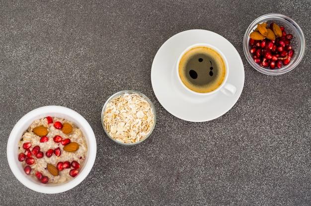 Gezond eten, ontbijt. havermout met granaatappel en noten, zwarte koffie.