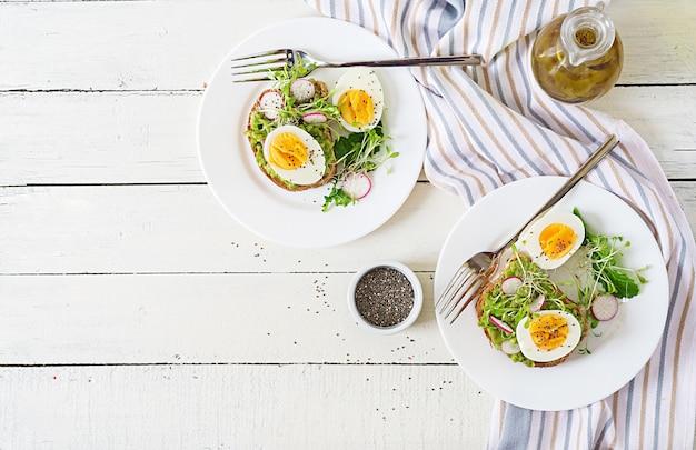 Gezond eten. ontbijt. het eisandwich van de avocado met geheel korrelbrood op witte houten achtergrond. bovenaanzicht. plat leggen
