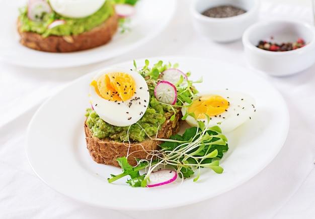 Gezond eten. ontbijt. het eisandwich van de avocado met geheel korrelbrood op witte houten achtergrond.