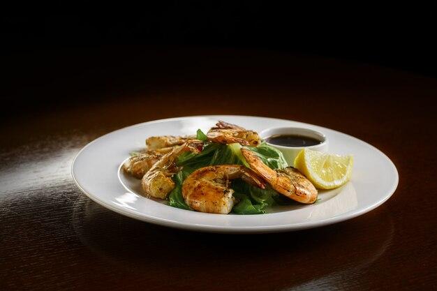 Gezond eten op de borden. lekkere garnalen met citroen, saus en kruiden