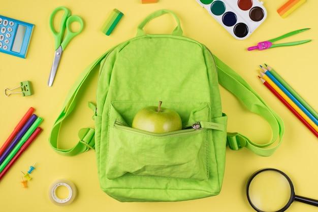 Gezond eten op school concept. boven boven bovenaanzicht foto van appelgroene rugzak kleurrijke briefpapier geïsoleerd op gele achtergrond