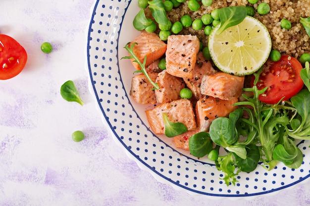 Gezond eten. plakjes gegrilde zalm, quinoa, groene erwten, tomaat, limoen en slablaadjes. plat leggen.