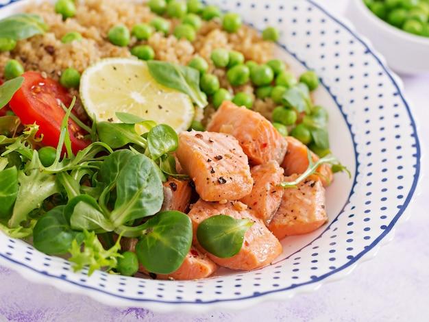 Gezond eten. plakjes gegrilde zalm, quinoa, groene erwten, tomaat, limoen en slablaadjes