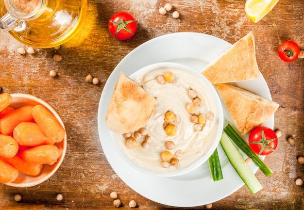 Gezond eten. plantaardige eiwitbronnen. kom hummus, op oud houten dienblad, met greens, gekookte en ruwe kikkererwten. met verse komkommer, tomaten, wortelen en broodpita. bovenaanzicht